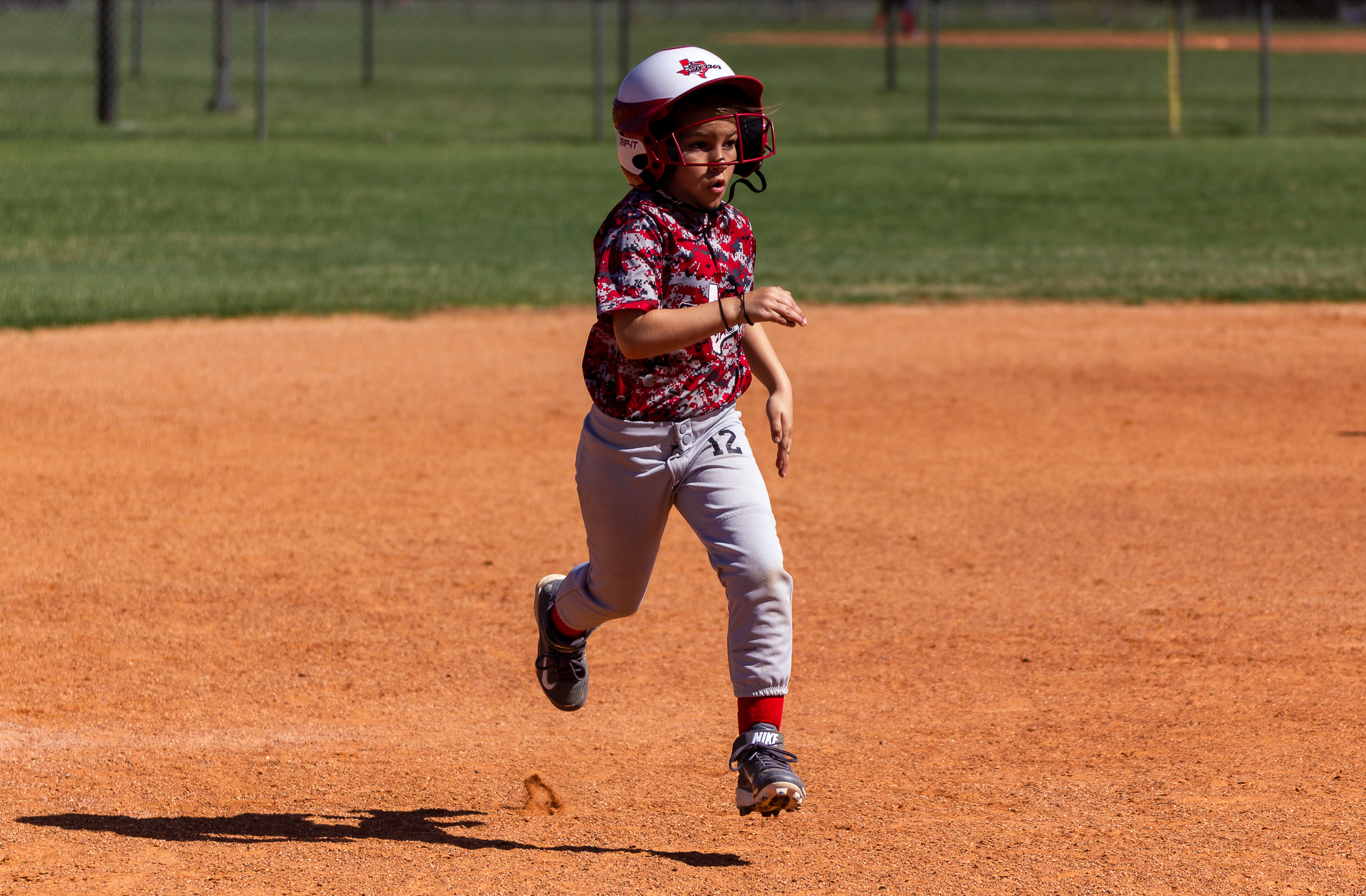 Young girl running the bases during a softball game